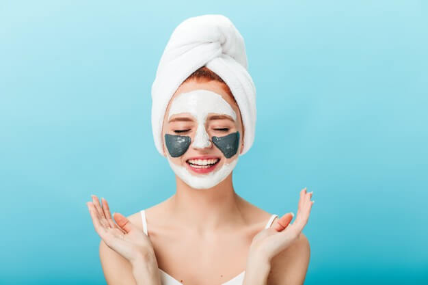 front view woman doing spa treatment with closed eyes studio shot charming girl with face mask standing blue background 197531 17852