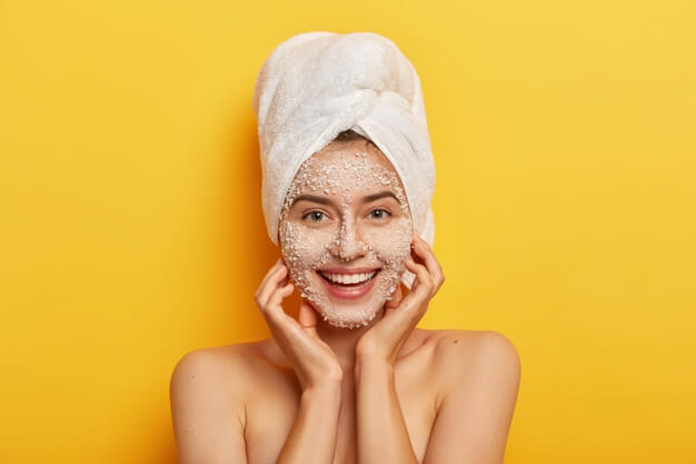 pleasant looking happy woman unclogges pores makes beauty step improve skin wears nourishing facial scrub supples complexion keeps hands cheeks 273609 30909