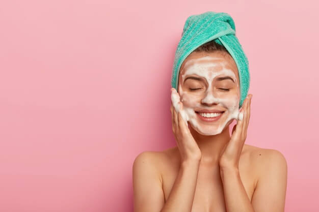pleased smiling woman washes face with cleansing gel has soap complexion keeps eyes shut wears wrapped towel head has naked body 273609 33472