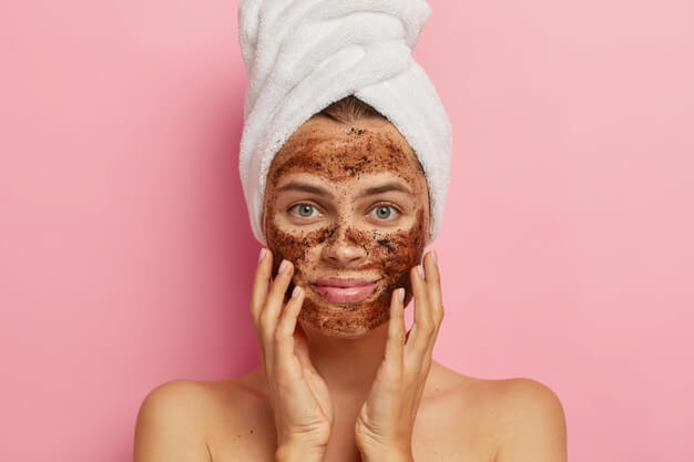 serious young lady applies coffee scrub face does peeling skin removes pores touches cheeks with hands has naked body 273609 30742
