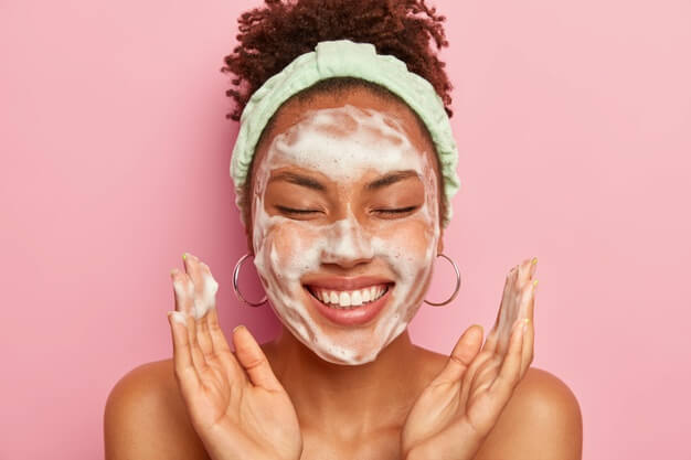 young woman raises palms face keeps eyes closed shows white teeth uses cleansing foam skin care gets real pleasure 273609 33241